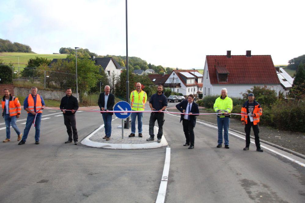 9 Leute schneiden symbolisch ein quer über die Fahrbahn gespanntes rot-weißes Band entzwei