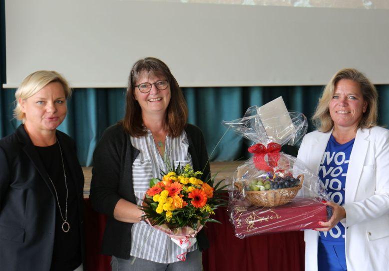 3 Frauen, die mittlere mit Blumenstrauß