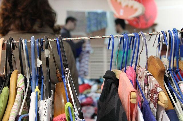 Gebrauchte Kleidung auf Kleiderbügeln, dahinter Menschen