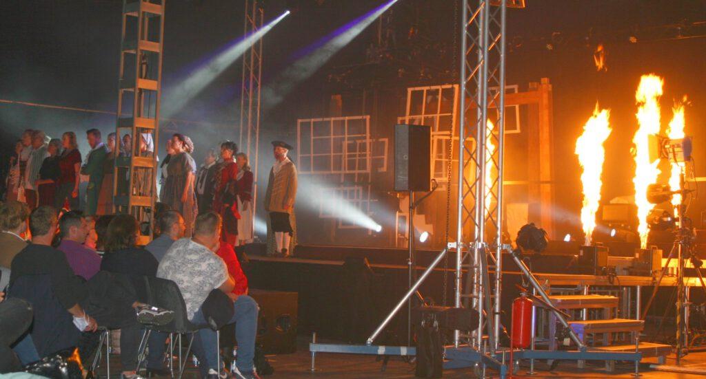 Darsteller auf der Bühne, im Hintergrund Feuer-Effekt