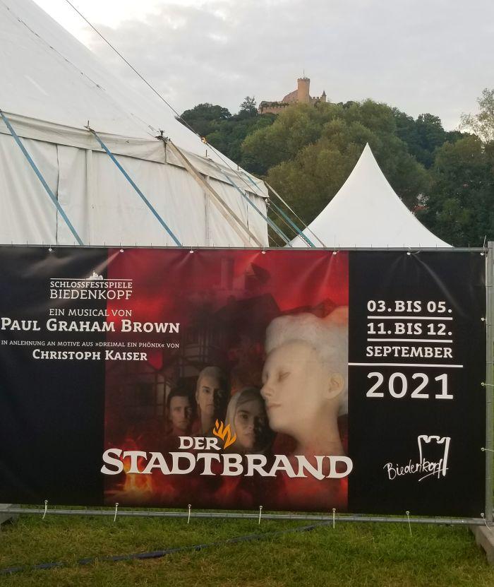 Plakat vom Stadtbrand vor dem Biedenkopfer Schloss im Hintergrund