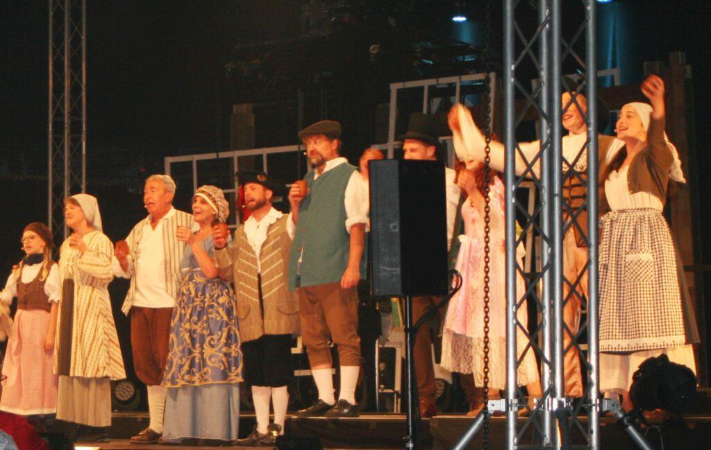 Darsteller singen und tanzen in historischen Kostümen