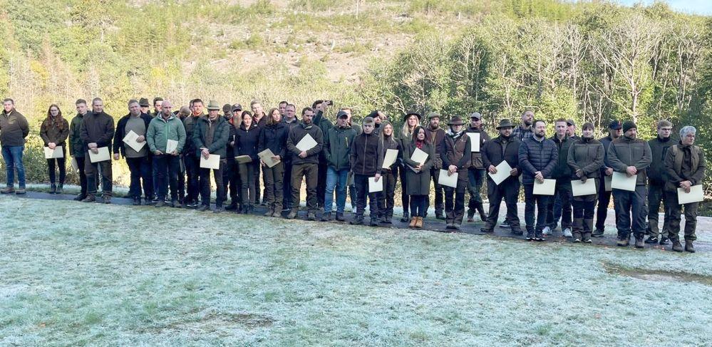 Haufenweise in Grün gekleidete Jägerinnen und Jäger in frostigem Waldstück