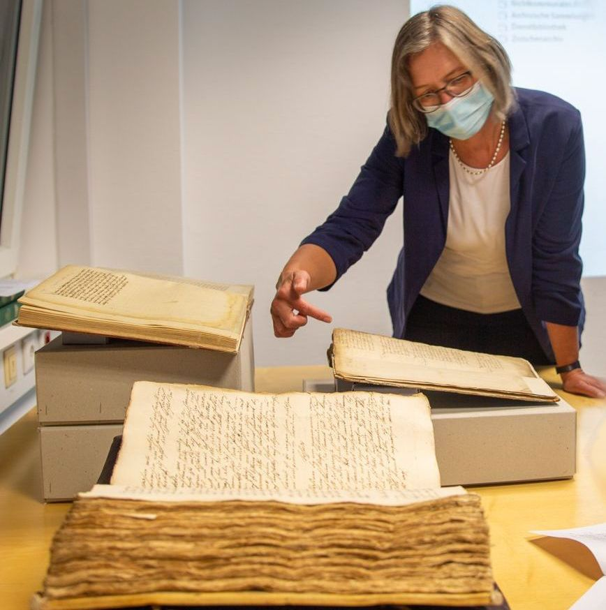 Frau um die 50 vor alten Büchern und Dokumenten