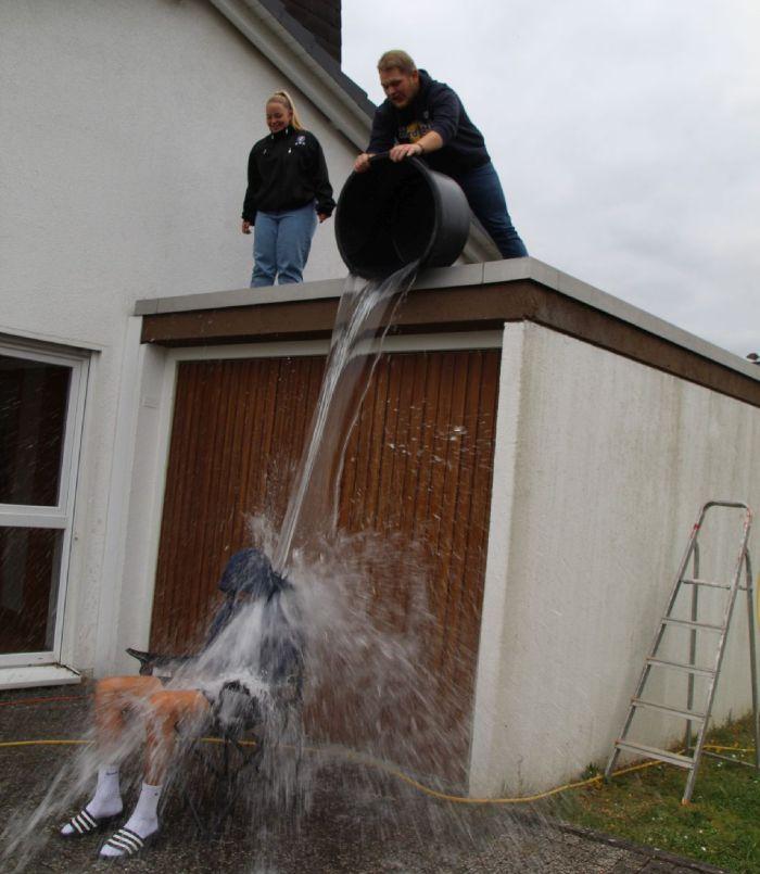 2 Leute schütten einen Eimer Wasser vom Dach aus auf einen Sitzenden